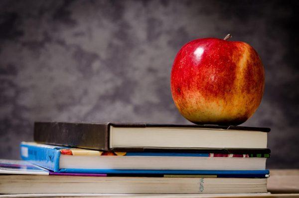 Czerwone-jablko-na-stosie-ksiazek