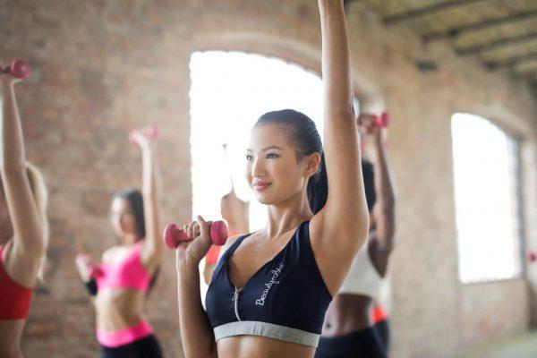 Dziewczyna trenująca na sali gimnastycznej z ciężarkami