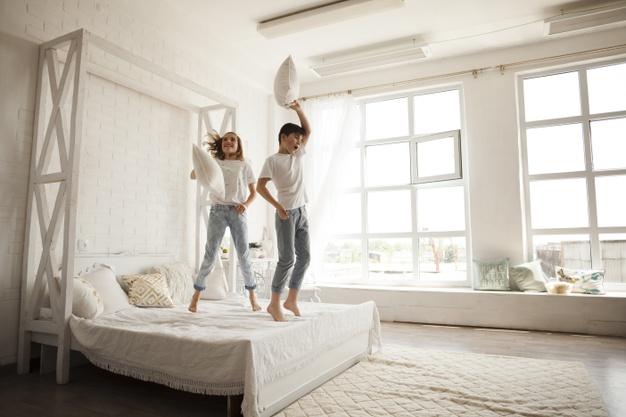 Para młodych ludzi skacząca po łóżku